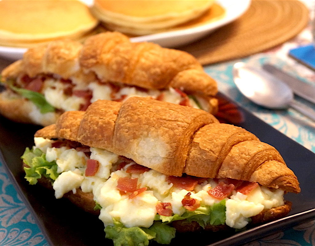 croissant sandwich with scrambled eggs cheese and bacon
